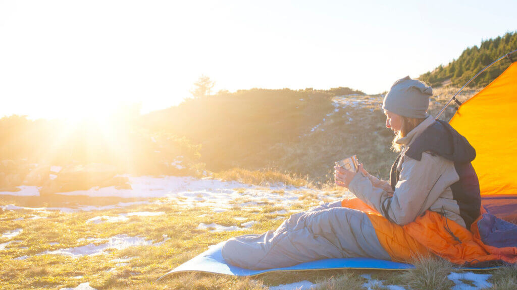 A woman sits outside of her tent in the sun while wearing a beanie, holding hot coffee, and bundled in her sleeping bag. There is snow on the ground around her tent and her sleeping bag.