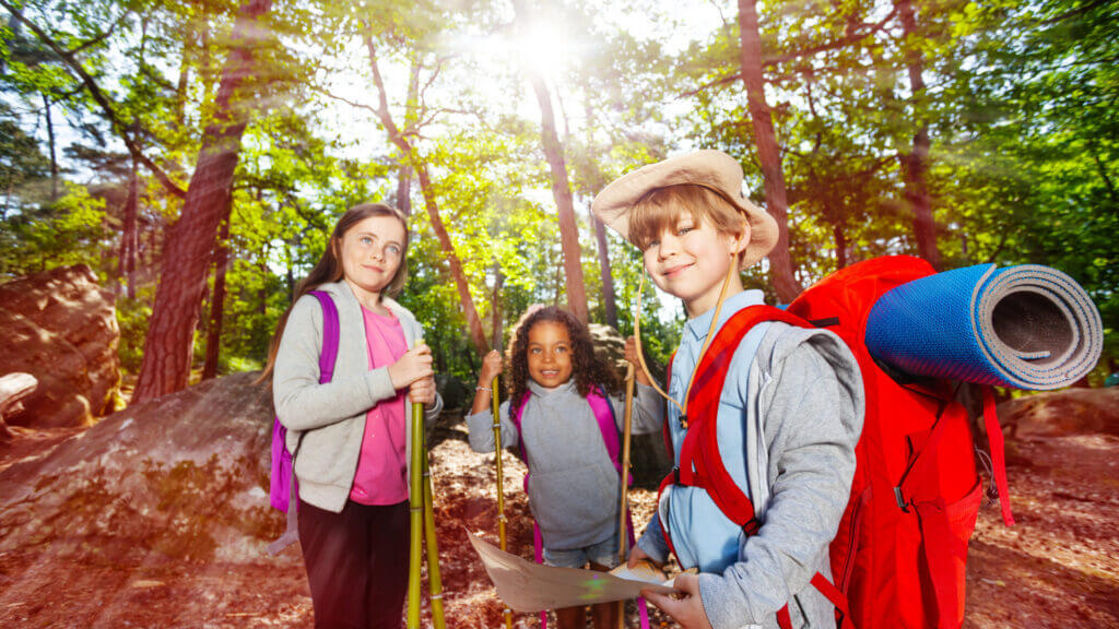 A young boy and two young girls are ready for a camping scavenger hunt. They have their camping gear in their backpacks, hiking poles, and a treasure map for their adventure.
