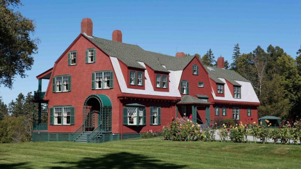 Image via the Maine Magazine. A red 'cottage' that FDR grew up going to in the summer off the coast of Maine. The cottage is actually very large with green shutters and doors, and roses line the walkway to the front door.