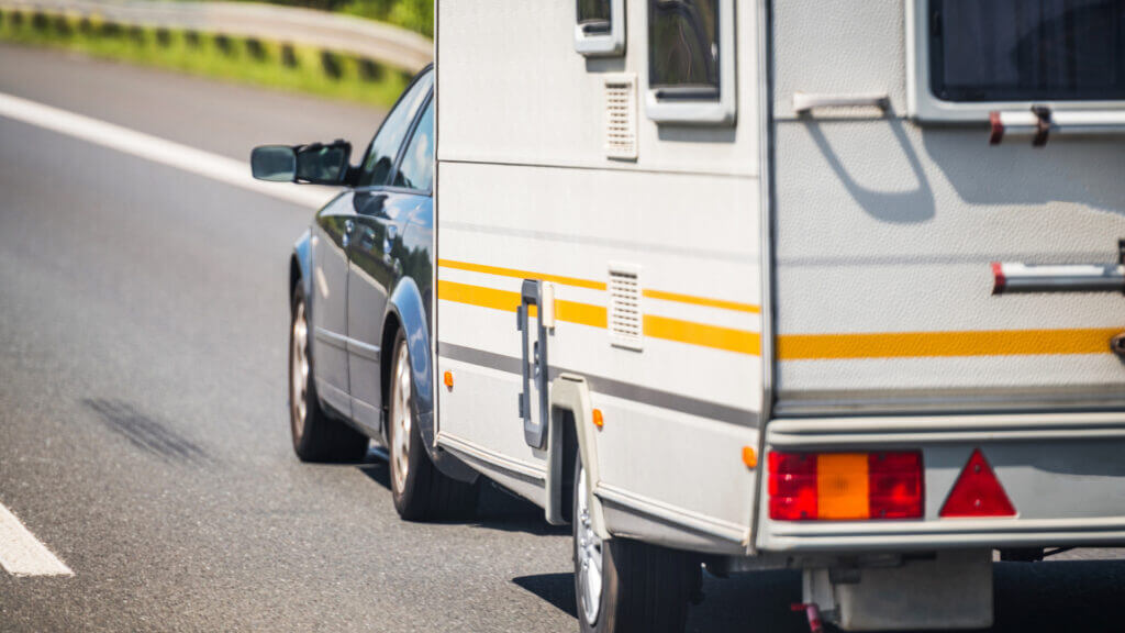A car pulls a white trailer along a highway. They are ready for the trip with the best trailer tires.