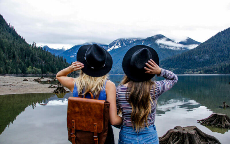 Two girls standing at edge of a lake in a national park while visiting on a free day.