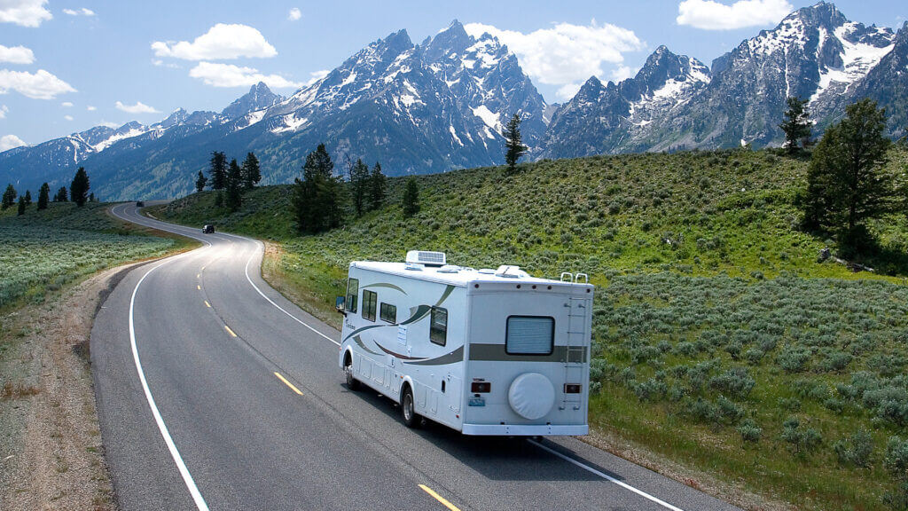 A white RV drives along a highway with the Grand Tetons towering in the far background and green rolling hills alongside the road.