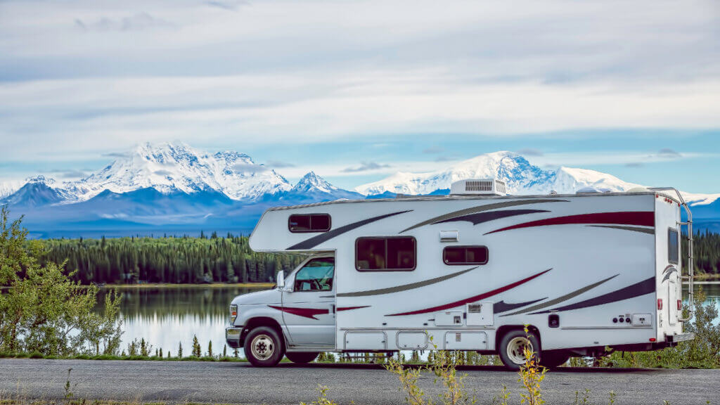A white RV is parked along a lake with trees and blue and snow-covered mountains in the background.