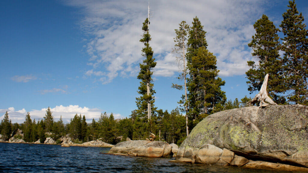 Large rocks, tall trees, and passing clouds hover above dark blue lake water at Union Valley Reservoir.