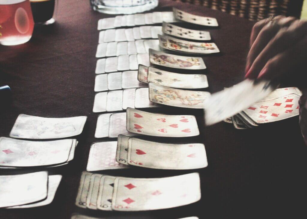 Old deck of cards laid out playing Solitaire. Cards are a great addition to you camping games.