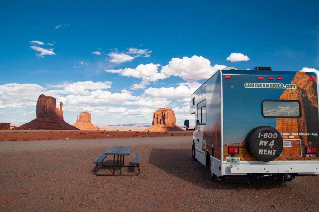 RV rental parked in the desert with a picnic table overlooking three mesas. While you may ask yourself can you lease an RV, you can rent.