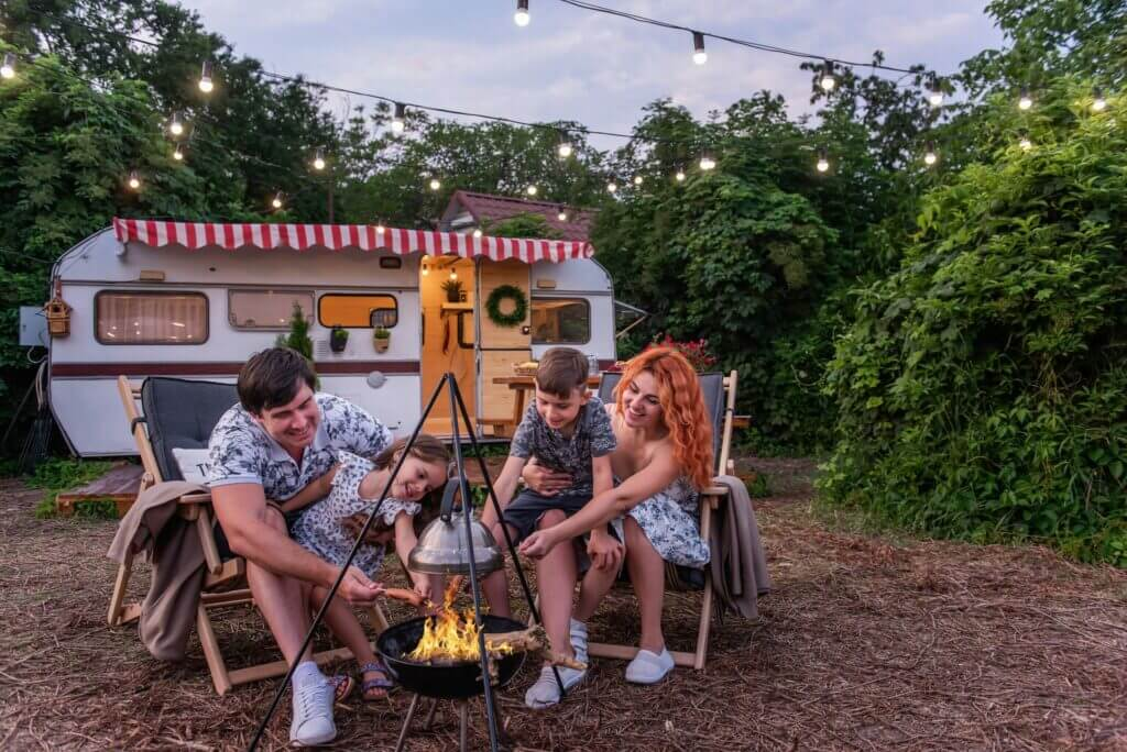 Family sitting in front of a fire roasting hotdogs with a small travel trailer in the background and string lights. This family asked can you lease an RV but discovered they could rent.