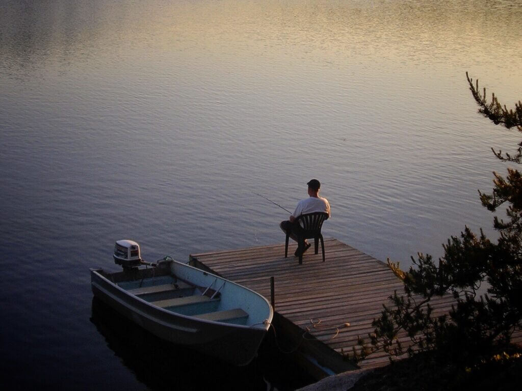 A man sitting in a chair on a dock with a small boat next to him. He has a fishing line in the water. Fishing is a great activity to partake in when Stampede Reservoir camping.