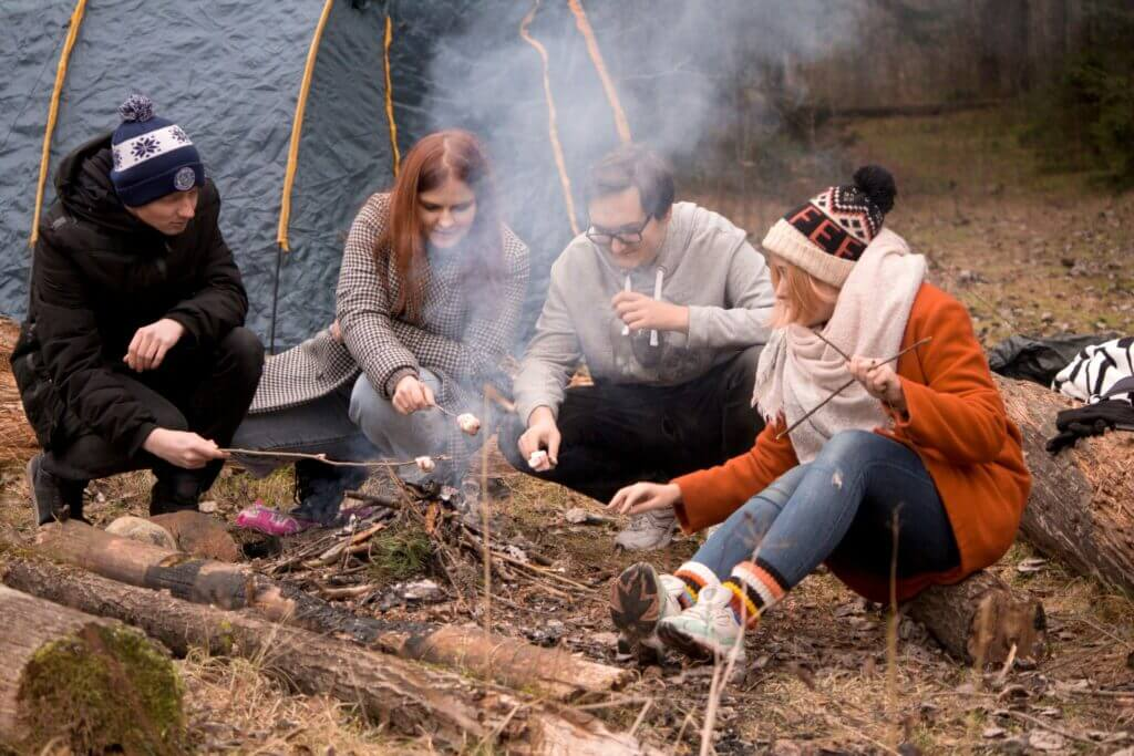 A group of young adults around a campfire roasting marshmallows. They are at a group site when Stampede Reservoir camping.