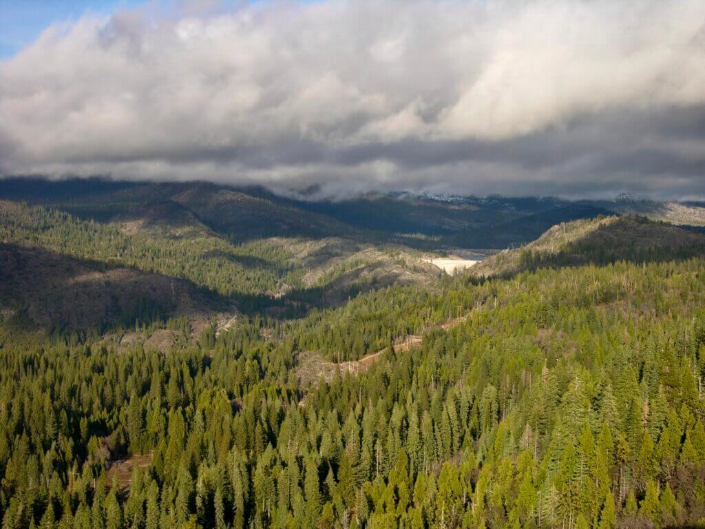 Shot of Tahoe National Forest with trees lining the mountains with plenty of clouds above. Stampede Reservoir camping is not far from this national forest.