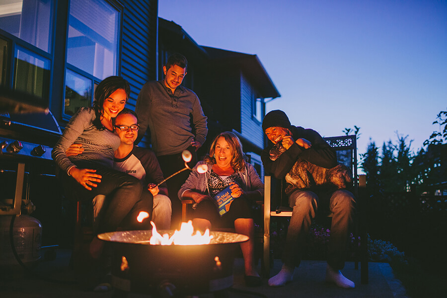 A family sitting in front of their portable propane fire pit roasting marshmallows and laughing.