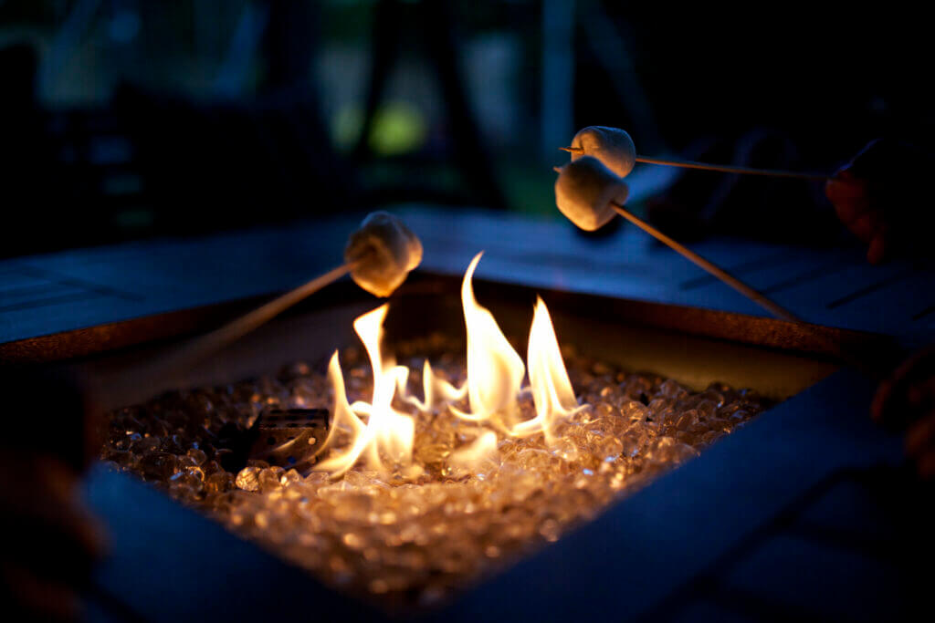 Three marshmallows roasting over a portable propane fire pit with glass decor