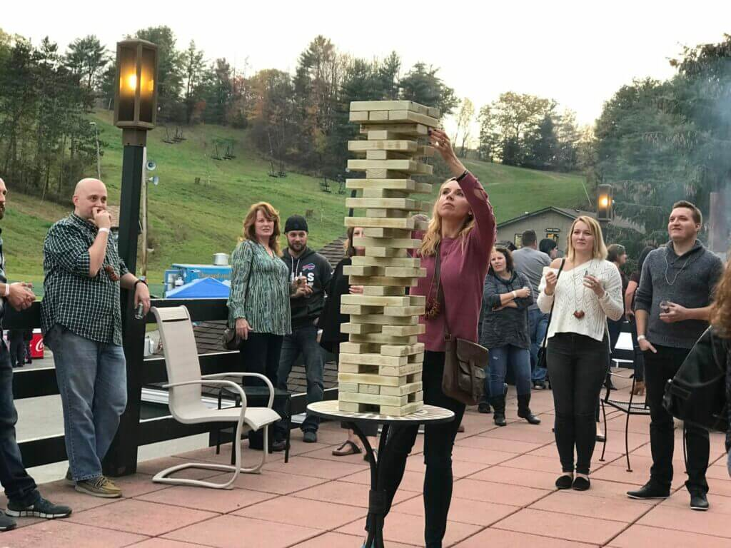 Woman playing giant Jenga with crowd watching behind her nervously. This game is a great addition to your perfect RV outside setup.