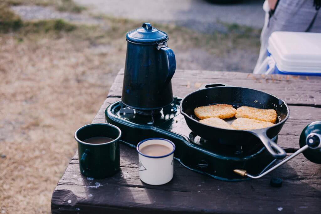 Picnic table with double burner on it. A kettle and cast iron pan with hashbrowns on are on the burners with two coffee cups next to it. You can have a yummy break like this when Pineview Reservoir camping.