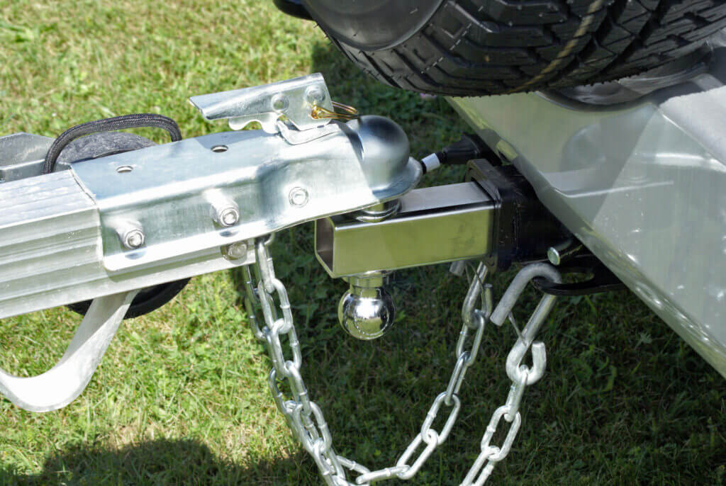 A trailer is secured to the back of a vehicle to be towed to its destination with a weight distribution hitch.