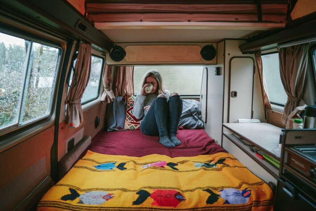 Woman sitting in her van sipping out of a mug looking out a rainy window. She's waiting in line to snag a first come first serve camping site.