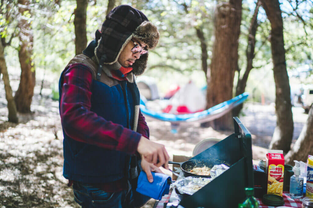 Man cooking breakfast at a portable grill in his campsite that he found using first come first serve camping tips