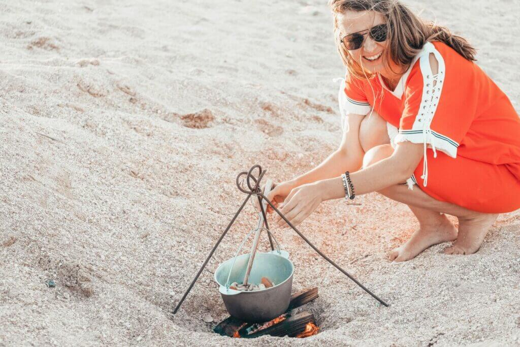 A woman on the beach cooking over an open flame. Enjoy times like this when Santa Cruz camping.