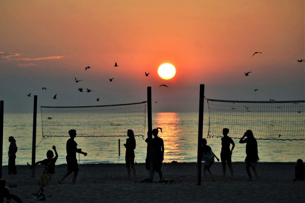 People playing beach volleyball with the sun setting over the water in the background. An activity you can take part in when Santa Cruz camping.