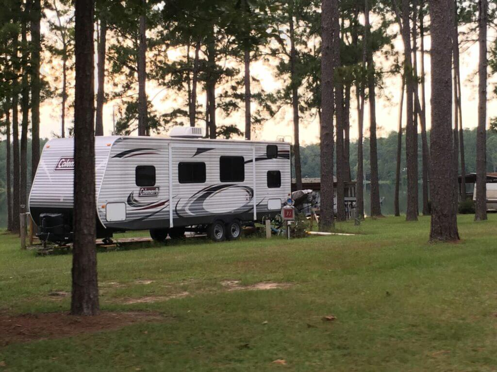 A travel trailer RV parked in a grassy area with trees around it. Finding RV parking is key when learning how to plan a road trip.
