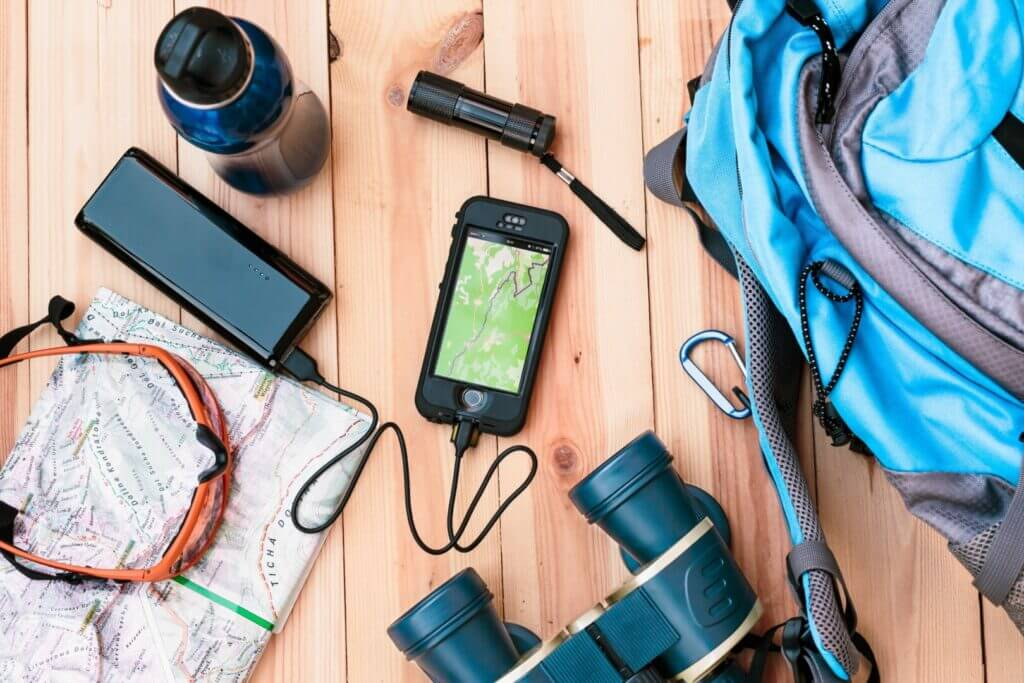 Road trip gear on a table getting ready to be packed into a backpack. Learn here how to plan a road trip so you don't forget anything.