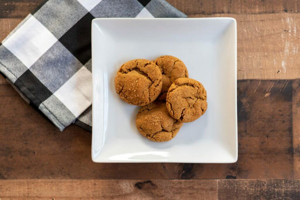 Ginger snap cookies sitting on a white plate with a black and white napkin underneath. These cookies were cooked in an RV microwave convection oven.