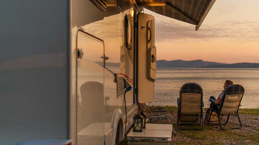 View from behind an RV with the door open with a woman sitting in a chair looking out onto a lake and mountains as the sunset lights glows.