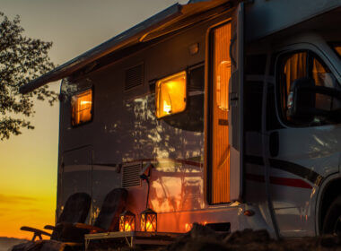 A parked RV with open windows and door parked next to a tree glows in the light orange light from the sunset.