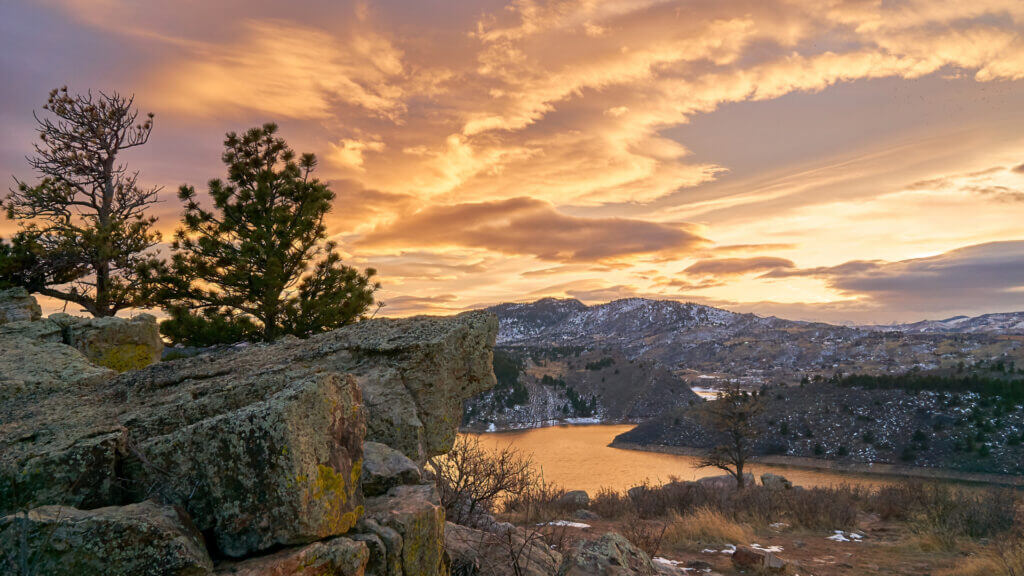 Horsetooth Reservoir water shines in the evening light with snow lightly covering the mountains, rocks, and trees.