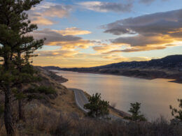 The sun sets over Horsetooth Reservoir and there are trees and a road in the foreground leading to great camping.