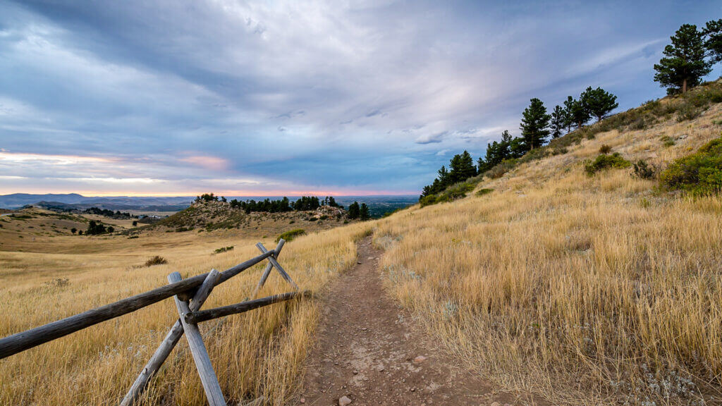 A dry golden brush trail weaves into the hills around Horsetooth Reservoir with a simple fence and trees in the distance.