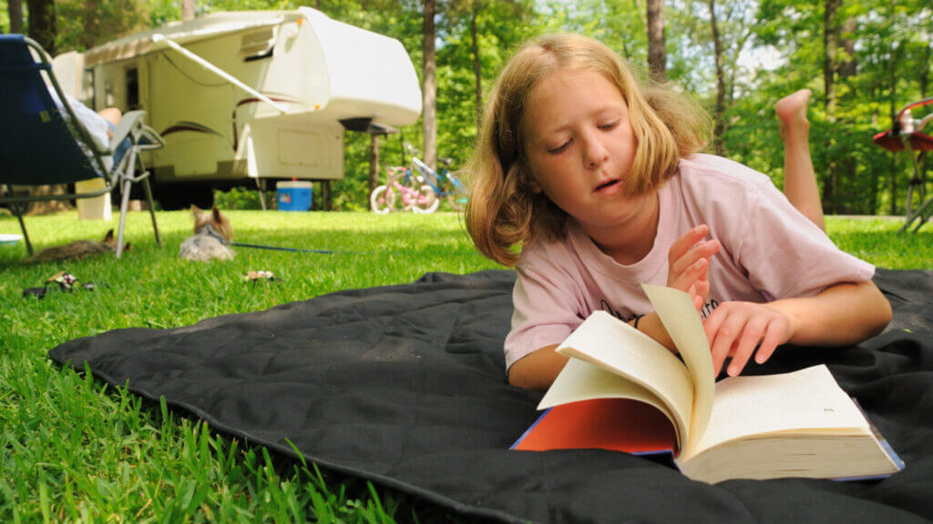 A young kid lays on an RV mat on the grass to read a book without getting a rash from the grass.