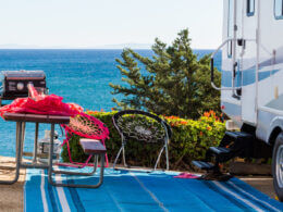 An RV camp is set up at the beach with a picnic table, chairs, and an outdoor mat.