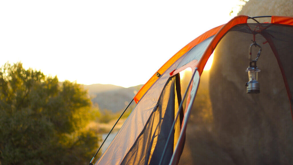 A close up shot of morning light coming through an orange tent camped along the shores of the san luis reservoir in central california.