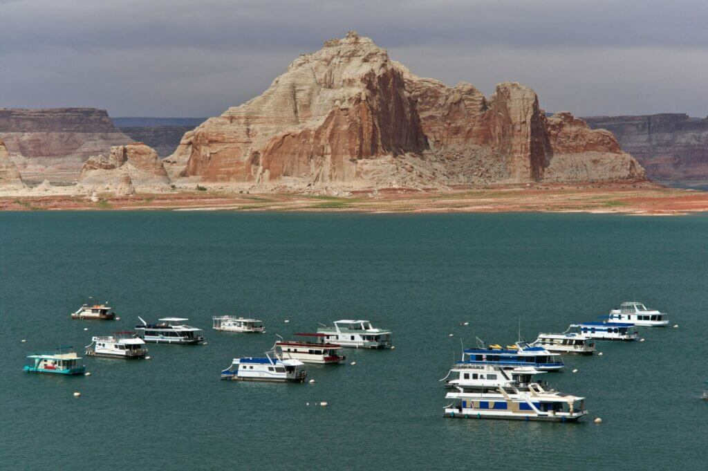 Aerial shot of Lake Powell with boats anchored at a marina. You can access views like this when Lake Powell RV camping.
