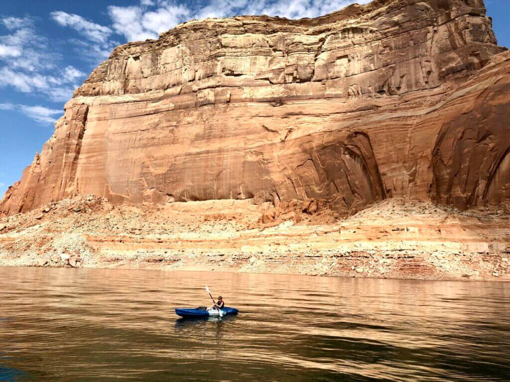 A man in a kayak on Lake Powell in front of a very tall rock formation. This is one of the activities you can partake in when Lake Powell RV camping.
