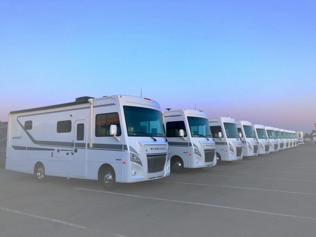 A line of Winnebago motorhomes parked in a row inside the factory parking lot.