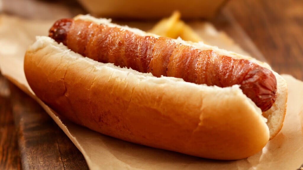 A delicious looking bacon wrapped hotdog in a bun sits on a wood table.