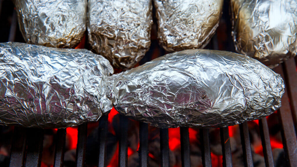 Hobo meals of potatoes and hamburger meat are wrapped in foil and roasting over a camping fire pit.