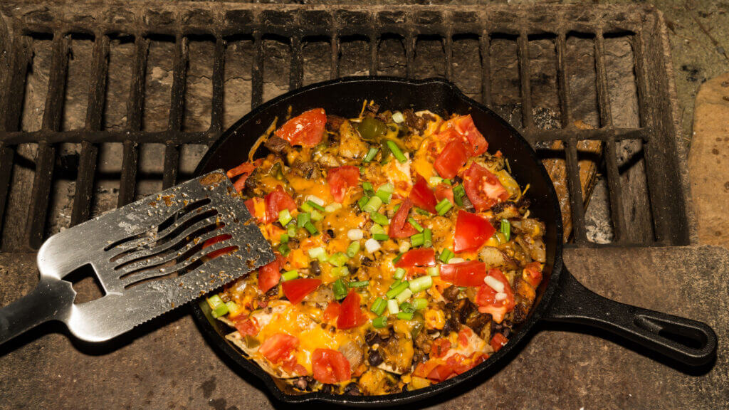 A cast iron pan cooks delicious nachos over a camping fire.