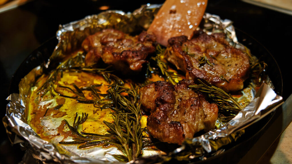 A foil lined pan cooks steak and rosemary for a delicious camping meal.