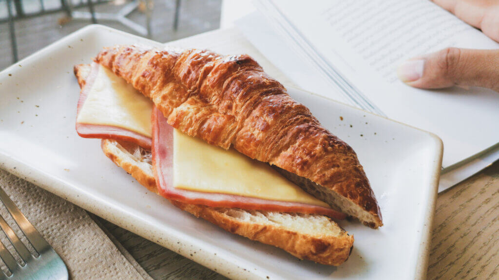 A hand holds a book open next to a hot ham and swiss croissant sandwich ready to enjoy.