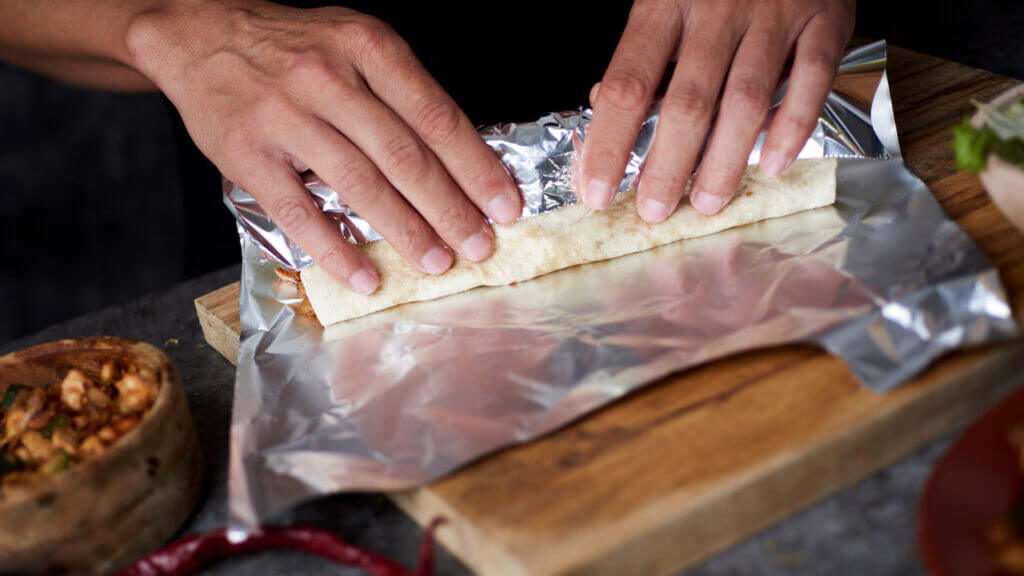 Hands are rolling a breakfast burrito up in foil to heat up over the campfire.