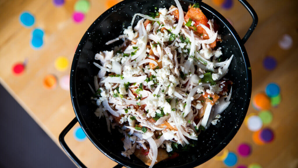A pan full of freshly made chilaquiles above a wooden table with confetti.