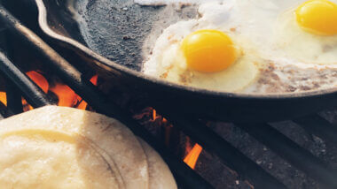 Delicious camping meal breakfast of eggs and tortillas over an open flame.