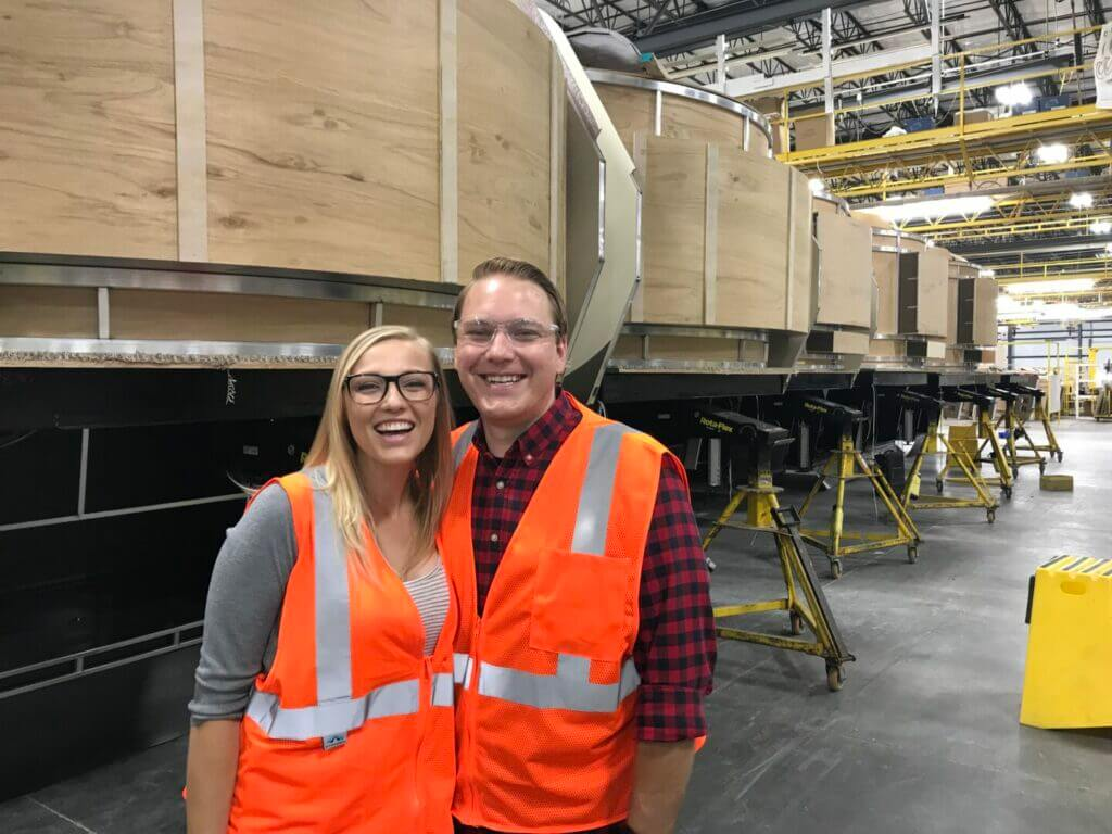 A man and woman smiling at the camera inside the Grand Design RV factory with unfinished fifth wheels in the background. With such a great customer service reputation, you might wonder who owns Grand Design RV.