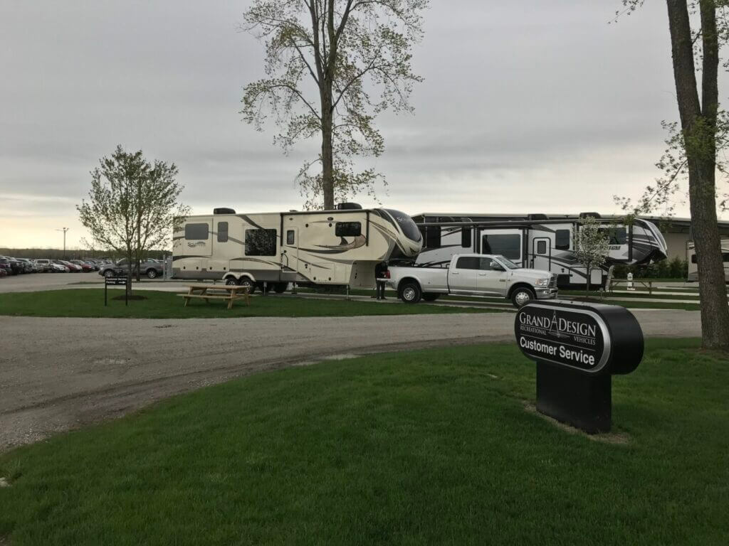 Fifth wheel RV with truck parked outside the Grand Design RV service center at sunset. With such a great customer service reputation, you might wonder who owns Grand Design RV.