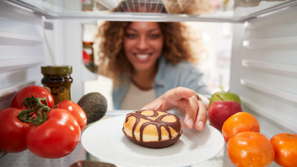 A woman reaches into a fridge full of veggies and fruits for a chocolate cheesecake type dessert with a smile on her face.