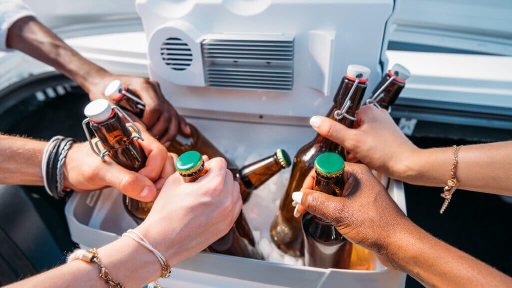 A variety of hands reach for beers that are cold from being in the portable refrigerator.
