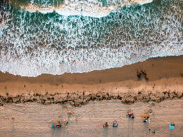 An overhead view of waves crashing on the shore with people sitting on the beach in San Diego which is a great place to beach camp in southern california.